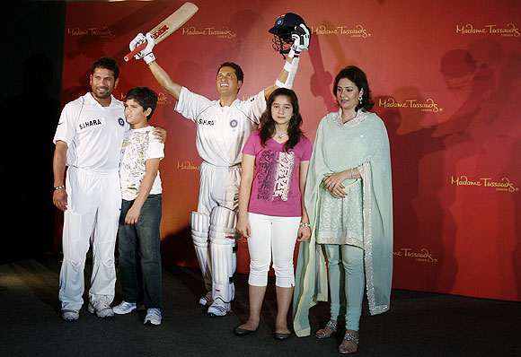 Indian cricketer Sachin Tendulkar (left), his son Arjun, daughter Sara and wife Anjali (right) pose with Sachin's new wax statue at Madame Tussauds museum, in London, on April 13, 2009