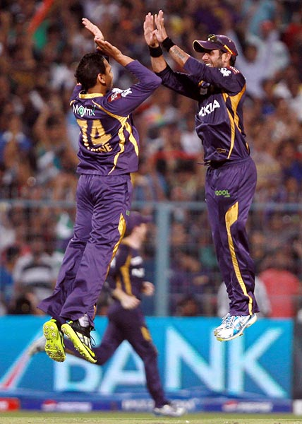 Sunil Narine celebrates with team mate Manoj Tiwary after getting the wicket of Dwayne Smith