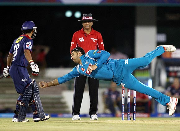 Yuvraj Singh tries to make a diving stop off his own bowling