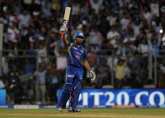 Rohit sharma captain of Mumbai Indians raises his bat after scoring a half century