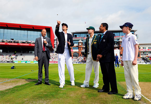 Captain Alastair Cook of England tosses the coin, watched by Australia captain Michael Clarke, commentator Nasser Hussain (L) and match referee Ranjan Madugalle