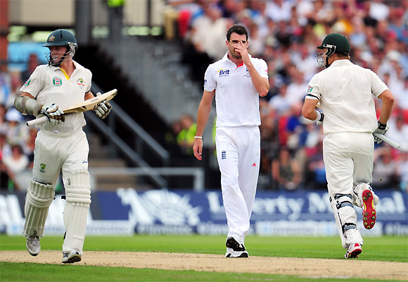 James Anderson reacts as Chris Rogers (left) and Shane Watson run between the wickets