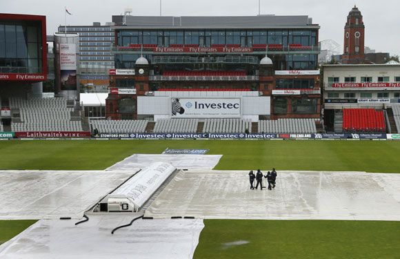 Ground staff brush water off the covers as rain falls on the pitch