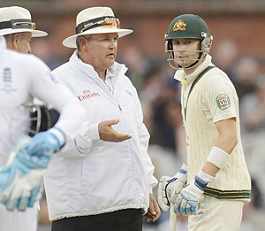 Australia's captain Michael Clarke speaks to umpire Marais Erasmus on the field after they sent the teams off for bad light on Sunday
