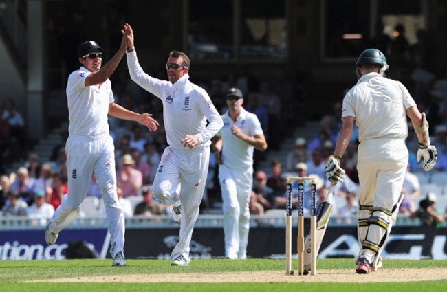 Graeme Swann of England celebrates the wicket of Chris Rogers of Australia with Alastair Cook (left)