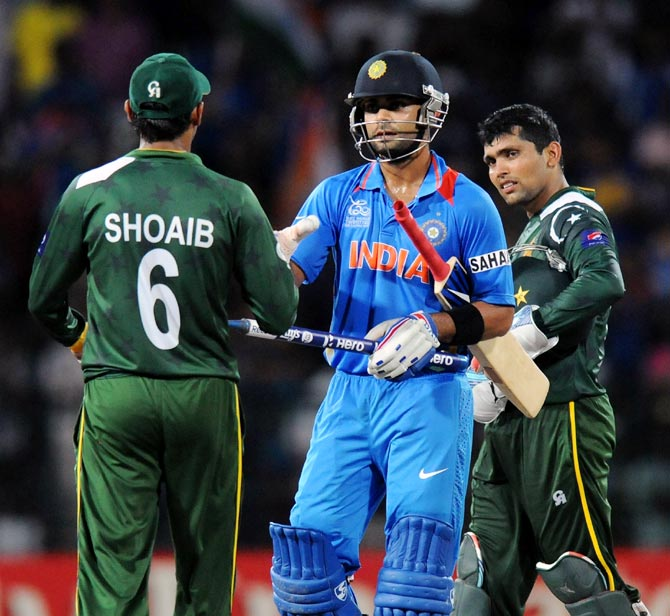 Virat Kohli (centre) with Shoaib Malik (left) and Kamran Akmal