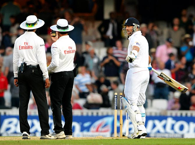 Matt Prior of England (right) speaks to umpires Aleem Dar and Kumar Dharmasena