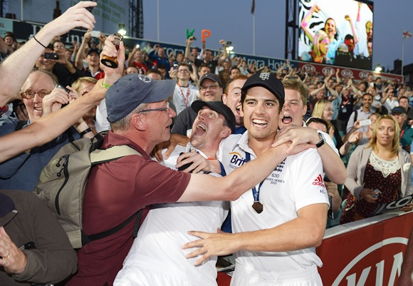 Kevin Pietersen and Alastair Cook of England celebrate with fans