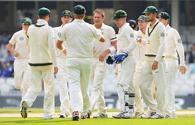 Ryan Harris celebrates with team mates after claiming the wicket of Chris Woakes on Sunday