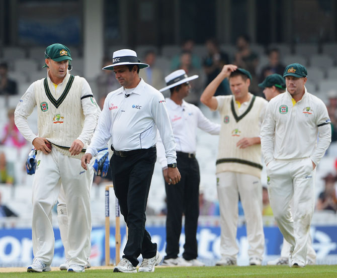 Michael Clarke of Australia talks to umpire Aleem Dar as he walks out into the field with team mates during day five