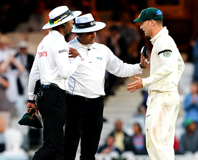 Australia captain Michael Clarke (right) speaks to umpires Aleem Dar and Kumar Dharmasena