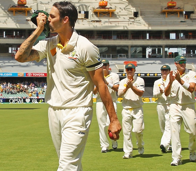 Mitchell Johnson of Australia kisses his cap as he leads his team from the field after bowling out England