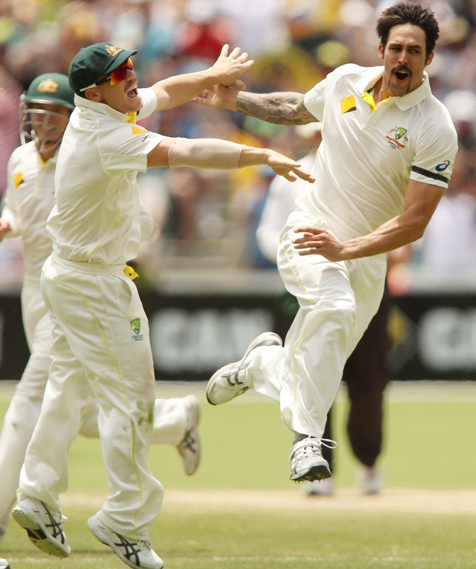 David Warner of Australia congratulates teammate Mitchell Johnson after he got the wicket of Stuart Broad