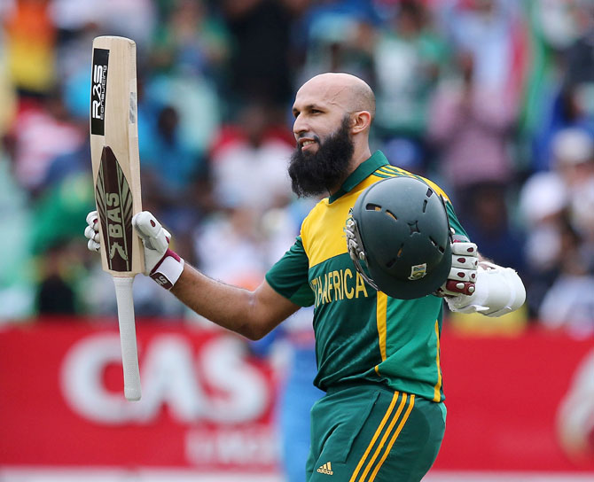 Hashim Amla raises his bat to acknowledge the applause following his hundred.