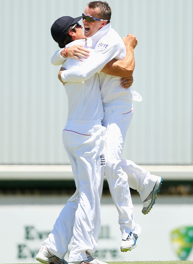Graeme Swann of England hugs Alastair Cook after catching Michael Clarke of Australia