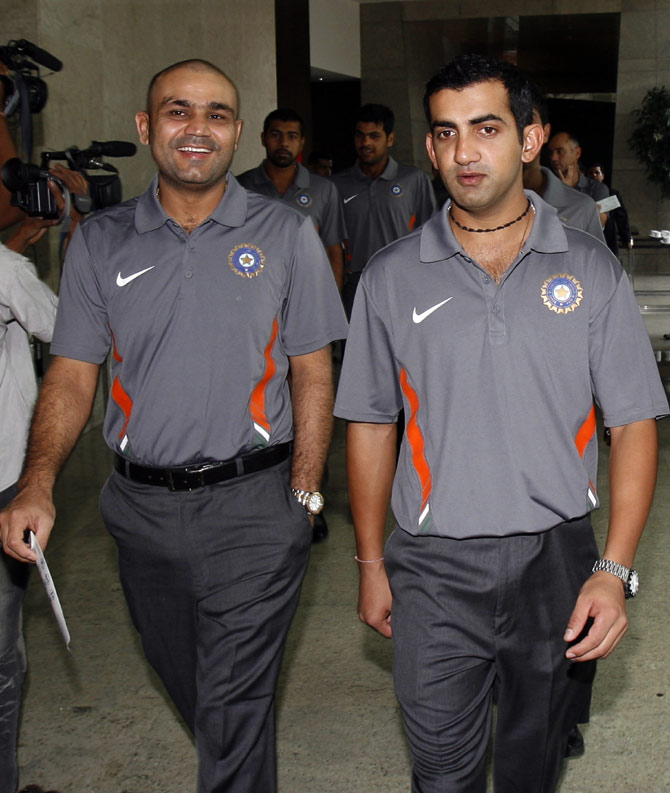 Virender Sehwag (left) and Gautam Gambhir arrive to pose for a team picture