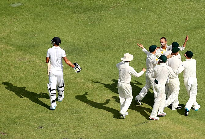 Australia's players celebrate as Kevin Pietersen walks back after his dismissal