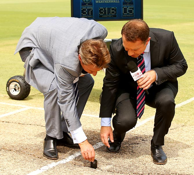Television commentators Ian Healy (left) and Michael Slater place a mobile phone into a crack on the pitch before start of play on day four