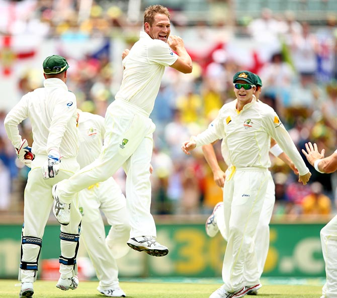 Ryan Harris (centre) celebrates the wicket of Alastair Cook