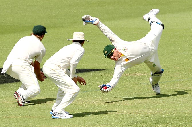 Australia wicketkeeper Brad Haddin (right) takes a catch to dismiss Joe Root