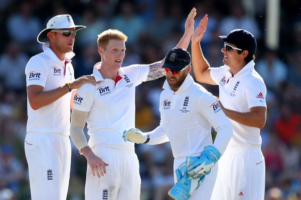 Ben Stokes and Alastair Cook of England celebrate the wicket of Brad Haddin