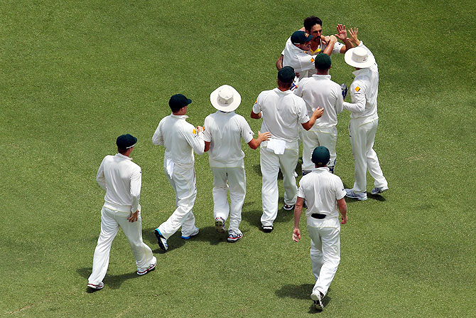 Mitchell Johnson of Australia celebrates with his teammates after taking the wicket of Matt Prior of England on Tuesday