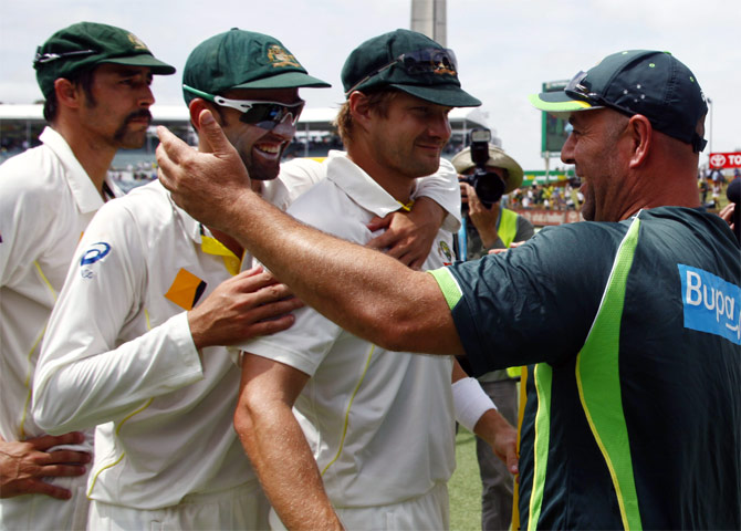 Australia's Mitchell Johnson (left), Nathan Lyon (2nd left) and Shane Watson prepare to hug coach Darren Lehmann