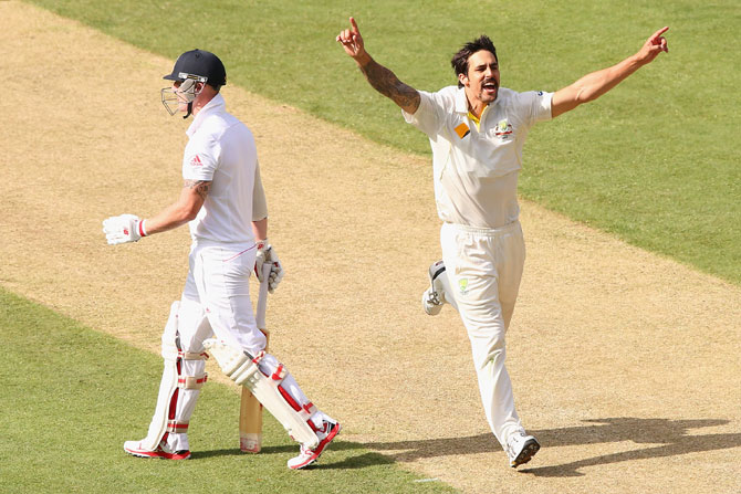 Mitchell Johnson of Australia celebrates taking the wicket of Ben Stokes of England