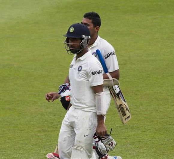 India's Cheteshwar Pujara and Murali Vijay walk back to the pavillion
