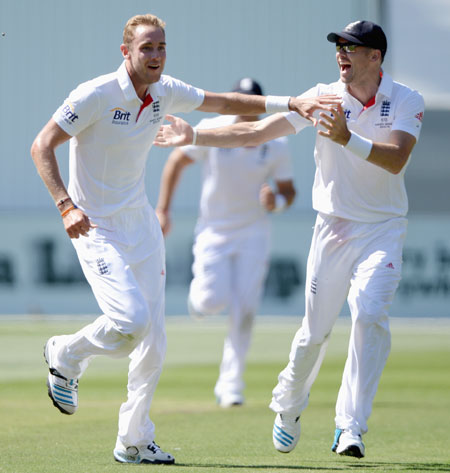 Stuart Broad of England celebrates with James Anderson after dismissing Steve Smith of Australia