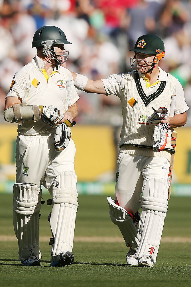 David Warner (right) and Chris Rogers of Australia walk off at t