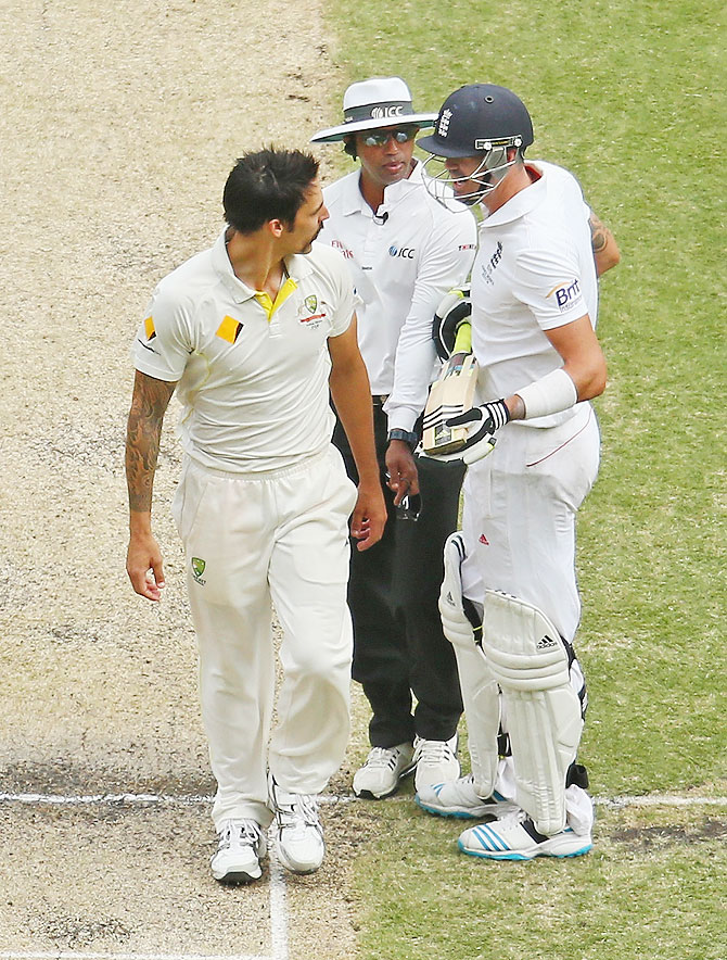 Kevin Pietersen of England and Mitchell Johnson of Australia exchange words as umpire Kumar Dharmasena intervenes on Saturday