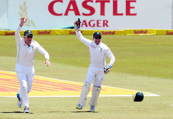 Graeme Smith and AB de Villiers of South Africa celebrate the wicket of Cheteshwar Pujara for 70 runs
