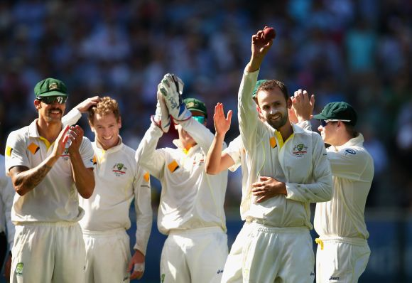 Nathan Lyon of Australia raises the ball after taking his fifth wicket