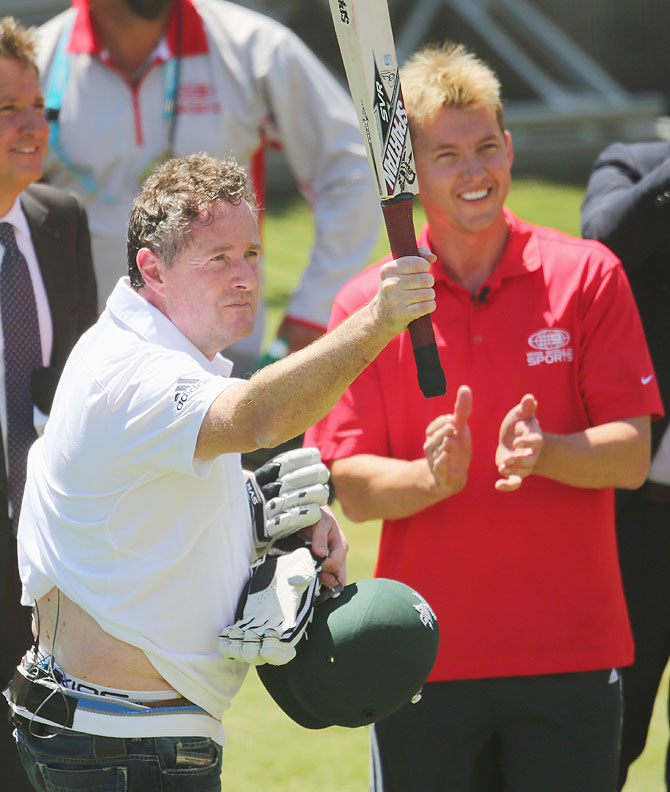 Piers Morgan salutes the crowd after facing deliveries from former Australian cricketer Brett Lee (right) in the nets during day two of the Fourth Ashes Test at Melbourne Cricket Ground on Friday