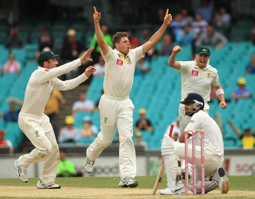 James Pattinson of Australia celebrates with team mates Shaun Marsh (L) and David Warner (R) after taking the wicket of Virat Kohli