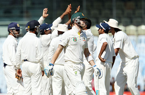 Indians celebrate as Australia captain Michael Clarke walks off after his dismissal