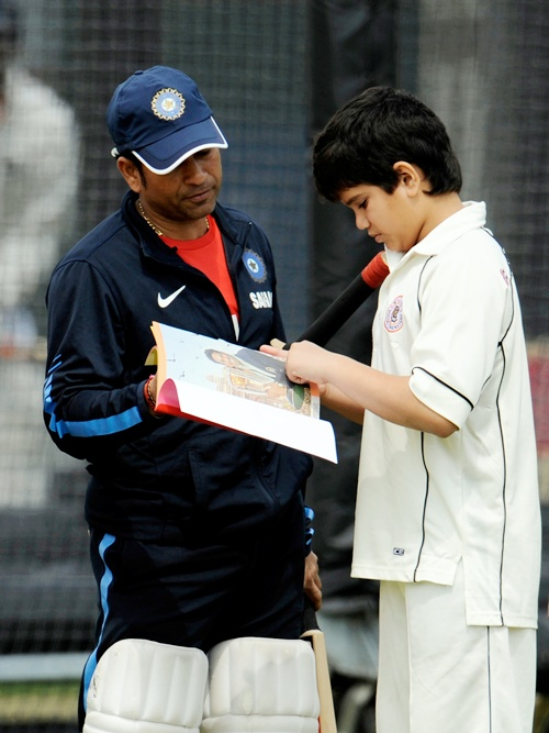India's Sachin Tendulkar looks at a book with his son Arjun