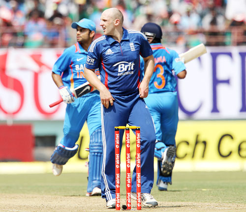 James Tredwell looks on as Virat Kohli and Suresh Raina cross over