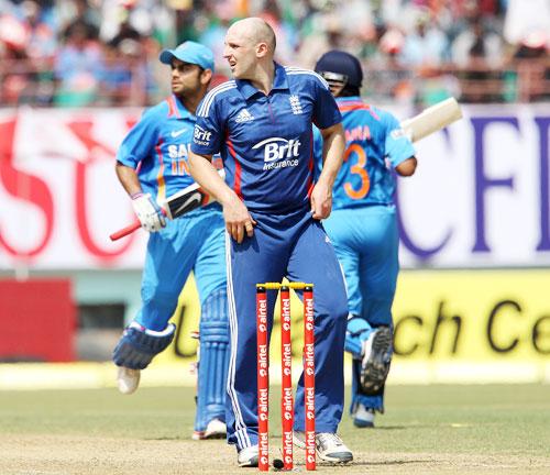 James Tredwell looks on as Virat Kohli and Suresh Raina cross over