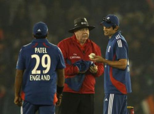 Umpire Steve Davis talks to England skipper Alastair Cook