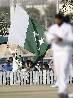 A Pakistan fan waves a flag during a cricket match