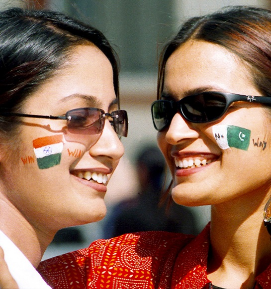Indian cricket fans with their faces painted with national flags of India (left) and Pakistan