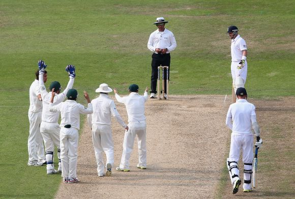 The Australian players look on after Umpire Aleem Dar turned down an appeal against Stuart Broad of England during day three of the 1