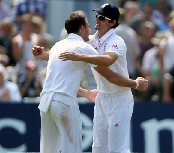 England captain Alastair Cook celebrates after taking the catch to dismiss Mitchell Starc with bowler James Anderson