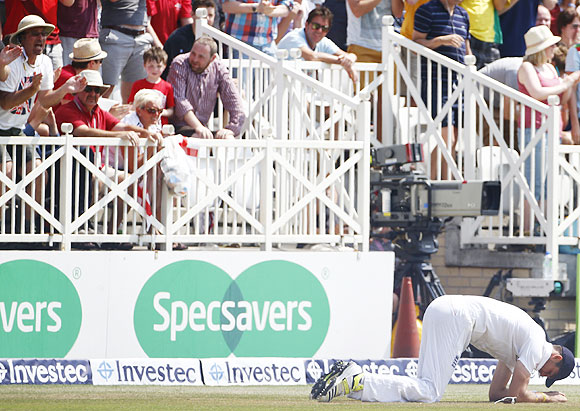 England's Steven Finn reacts after dropping Australia's Brad Haddin