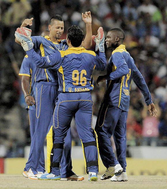 Rayad Emrit and Umar Akmal of Barbados Tridents celebrate the wicket of St. Lucia Zouks' Herschelle Gibbs at Kensington Oval in Bridgetown, Barbados, on Tuesday