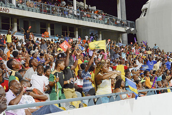 Fans cheer their team during the opening match of the Cricket Caribbean Premier League between Barbados Tridents and St Lucia Zouks at Kengsinton Oval in Bridgetown, Barbados, on Tuesday