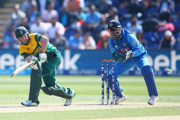 AB de Villiers (L) of South Africa plays to the legside as wicketkeeper MS Dhoni (R) of India looks on
