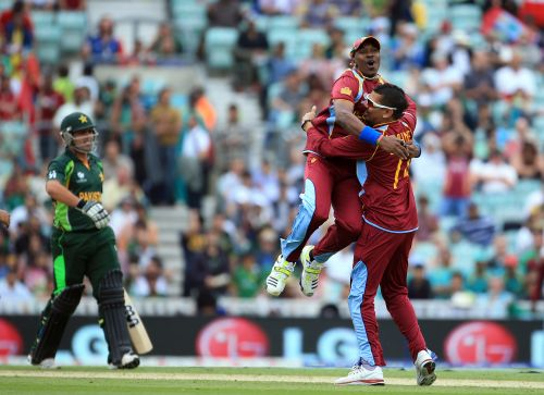 Sunil Narine is congratulated by Dwyane Bravo after he takes the wicket of Kamran Akmal